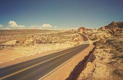 老影片减速火箭的样式绕沙漠路 免版税库存照片