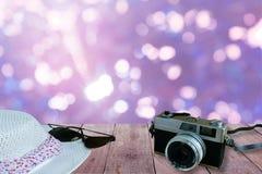 老影片照相机、太阳镜和帽子在老木桌前景有被弄脏的蓝色bokeh背景 免版税库存图片