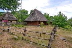 老房子在乡下在茅屋顶下 使用一个小庭院和片状木篱芭 免版税库存照片