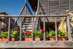 老房子的木楼梯巴尔干样式的与对此的红色大竺葵沿扶手栏杆 免版税图库摄影