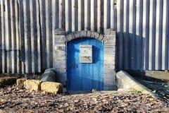 老房子的蓝色门在村庄 免版税库存图片