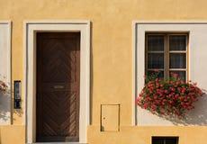 老房子的黄色门面 入口木门和窗口 库存照片