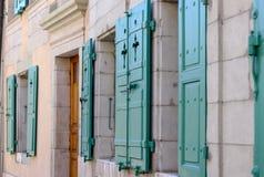 老房子门面有窗口的与开放绿色快门和木门 图库摄影