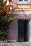老房子门面有绿色灌木的 打开前门 免版税库存照片