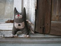 老房子风化了与滑稽的纺织品猫的木头开窗口 免版税库存照片