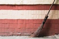 老手工制造街道的笤帚对砖墙 免版税图库摄影