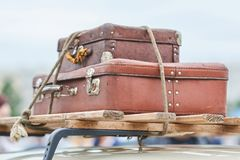 老手提箱被栓对汽车的屋顶 免版税库存图片