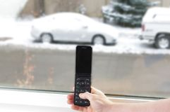 老手机在手中有在雪的汽车的 库存照片
