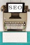 老打字机、新的键盘和片剂个人计算机有文本& x22的; SEO& x22; 库存照片