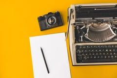 老打字机、葡萄酒影片照相机、纸片和在黄色背景,顶视图的一支铅笔 创造性的概念 库存图片