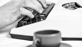 老打字机和作者手 使用白色葡萄酒打字机设备关闭的男性手类型故事或报告 库存图片