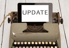 老打字机和新的片剂个人计算机有词& x22的; UPDADE& x22;在木背景 库存图片