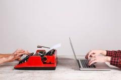 老打字机和膝上型计算机在桌上 技术进展的概念 免版税图库摄影