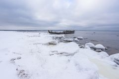 老打破的小船击毁和多岩石的海滩冬天 冻海,平衡在岸的轻和冰冷的天气象童话国家 库存图片