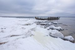 老打破的小船击毁和多岩石的海滩冬天 冻海,平衡在岸的轻和冰冷的天气象童话国家 免版税库存照片