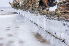 老打破的小船击毁和多岩石的海滩冬天 冻海,平衡在岸的轻和冰冷的天气象童话国家 图库摄影