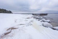 老打破的小船击毁和多岩石的海滩冬天 冻海,平衡在岸的轻和冰冷的天气象童话国家 库存照片