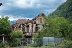 老打破的房子和多云天空背景 免版税库存图片
