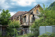 老打破的房子和多云天空背景 库存照片