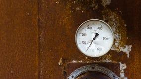 老打破的温度测量仪有生锈的背景 免版税库存照片