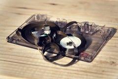 老打破的被解开的紧凑卡式磁带录音磁带在木背景弄糟了  库存照片