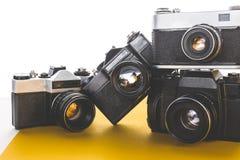 老技术概念 葡萄酒黄色表面,正面图上的影片照相机 免版税库存图片