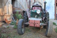 老拖拉机在村庄 库存照片