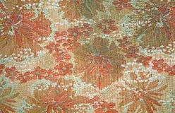 老挂毯织品的纹理与退色的红色花卉样式的 免版税库存照片