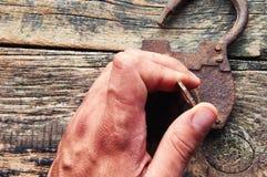 老挂锁和钥匙在木背景和人的手 免版税库存图片