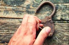 老挂锁和钥匙在木背景和人的手 免版税库存照片