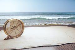 老指南针和地图和海浪 免版税库存照片