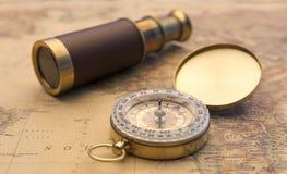 老指南针和老望远镜在葡萄酒映射世界探险家概念 免版税图库摄影
