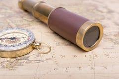 老指南针和老望远镜在葡萄酒映射世界探险家概念 库存照片