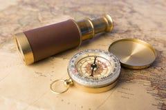 老指南针和老望远镜在葡萄酒映射世界探险家概念 免版税库存照片