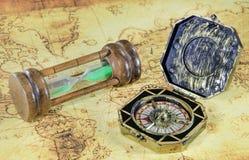 老指南针和滴漏在一个旧世界映射 库存照片