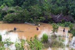 老挝人妇女抓住鱼在河。 免版税库存图片