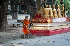 年轻老挝修士在宗教仪式以后清扫大桶Phiavat修道院。 免版税库存照片