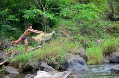老挝在塔德Yeang瀑布小河的儿童人民使用的捕鱼网抓住鱼  库存图片