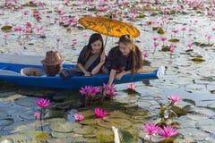 老挝妇女在花莲花湖,佩带传统泰国人,红色莲花海UdonThani泰国的妇女 免版税库存照片