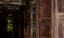 老损伤的门窗口在一个老损伤黑暗的房子里 库存照片