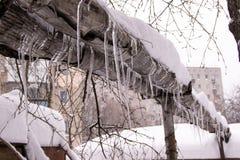 老损坏的管道用被冰的冰柱盖 库存照片