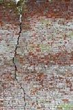 老损坏的红砖墙壁的纹理有一个大裂缝的 免版税图库摄影