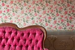 老损坏的红色长沙发在一个古色古香的房子里。在墙壁的花墙纸 免版税库存照片