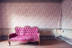 老损坏的红色长沙发在一个古色古香的房子里。在墙壁的花墙纸 图库摄影