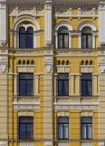 老损坏的黄色涂了灰泥有禁止的窗口的砖墙和 免版税库存图片