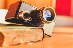 老摄象机和一本古色古香的书 免版税库存图片