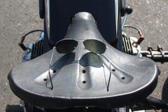 老摩托车马鞍和太阳镜 库存照片