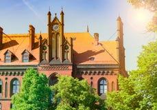 老教会由太阳,砖瓦房的美好的风景在树后的照亮 免版税库存图片