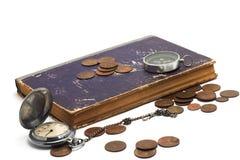 老时钟、书、指南针和硬币 免版税库存照片