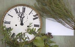 老时钟和空白纸在绿色木背景 与植物和紫色莓果的新年背景 新叶子和purpl 图库摄影